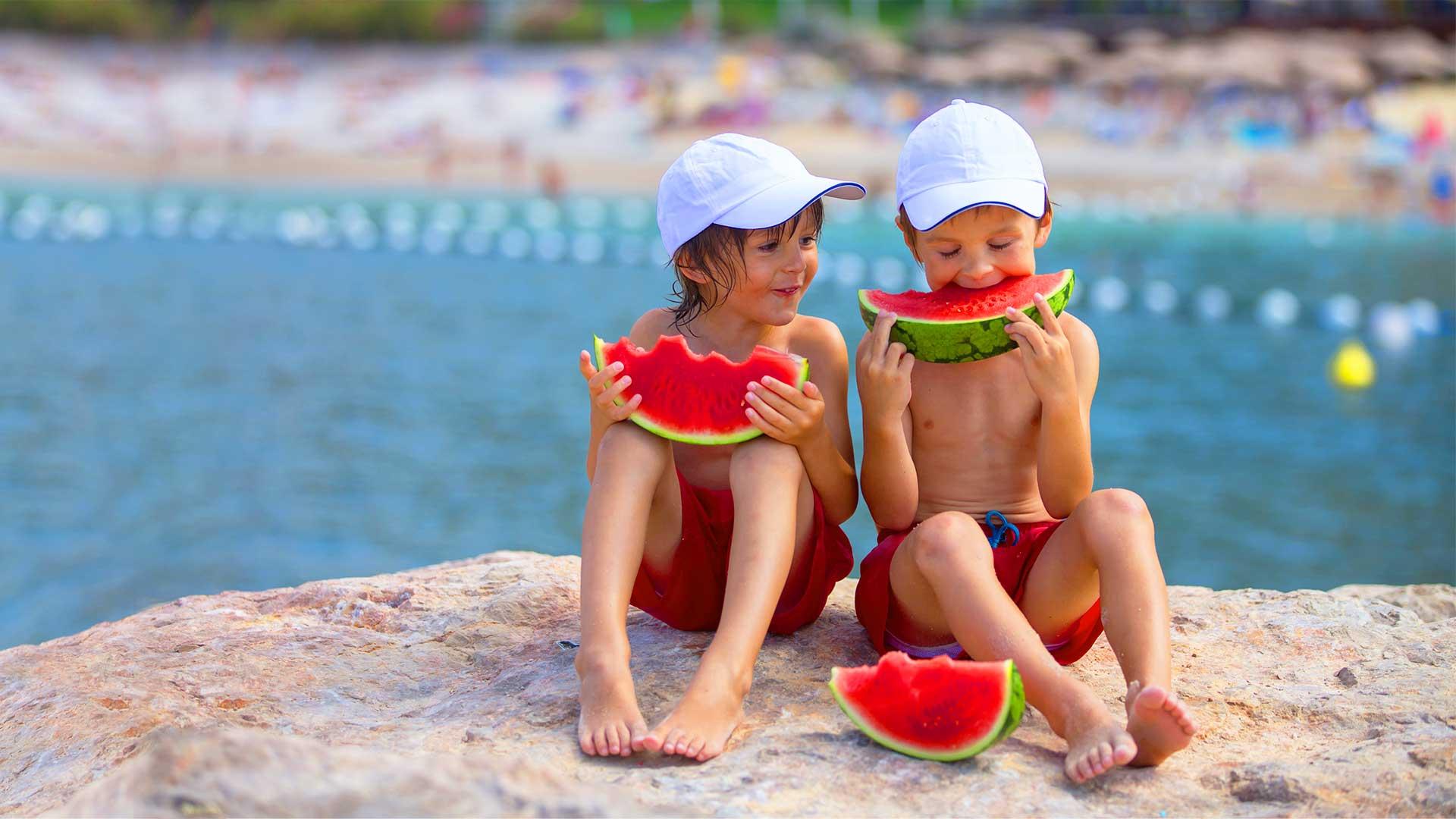 Prelazak na ljetnju sezonu Dijeca jedu lubenicu na kamenoj plaži more blog