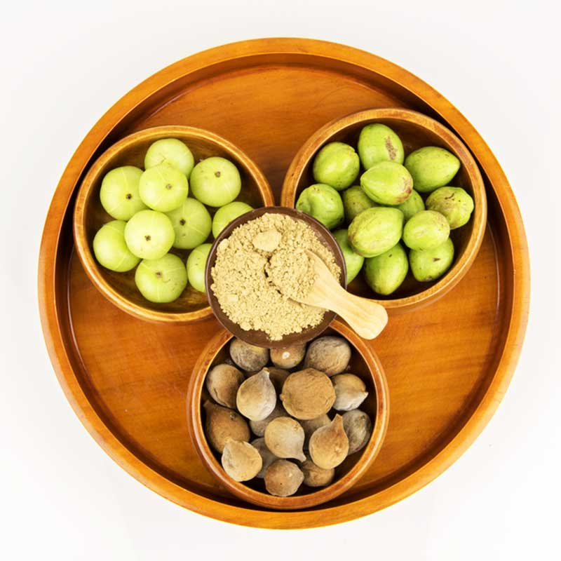 Triphala Amalaki Bibhitaki Haritaki svježi plodovi na tacni u zdjelama prah u zdjeli